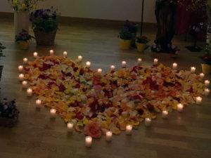 Herz aus Blütenblättern mit Kerzen
